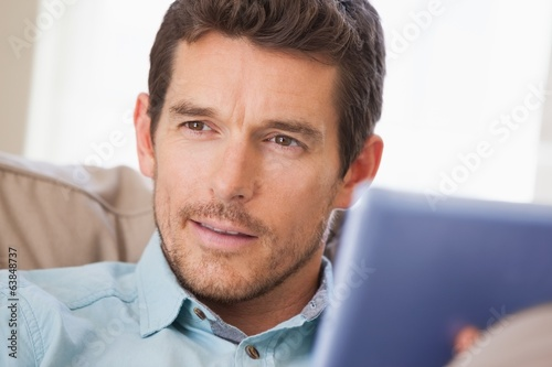 Man with digital tablet looking away at home