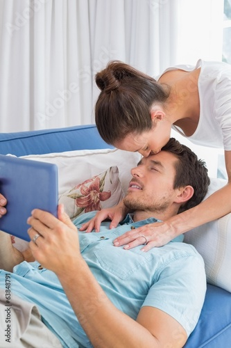 Woman kissing mans forehead while he uses digital tablet