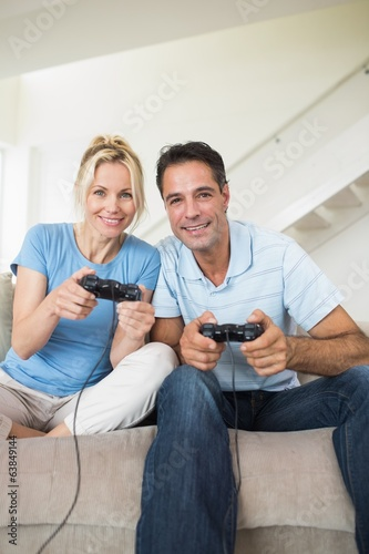 Cheerful couple playing video games in living room