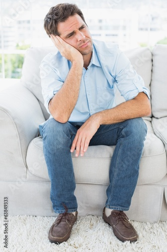 Unhappy man sitting on the couch looking away