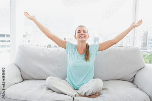 Cheerful woman sitting on couch with arms outstretched