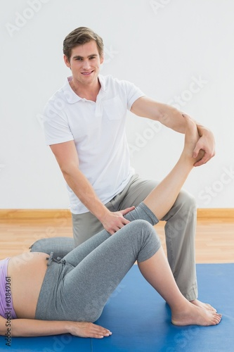 Personal trainer lifting pregnant clients leg