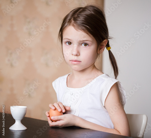 Serious prescholler girl holding egg in her hands