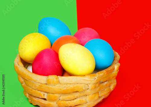 Baked basket with Easter colored eggs on the color background