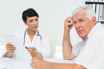 Doctor showing reports to worried senior patient