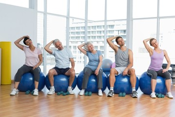 Class sitting on exercise balls and stretching neck in gym
