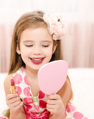 Cute little girl with lipstick and  mirror