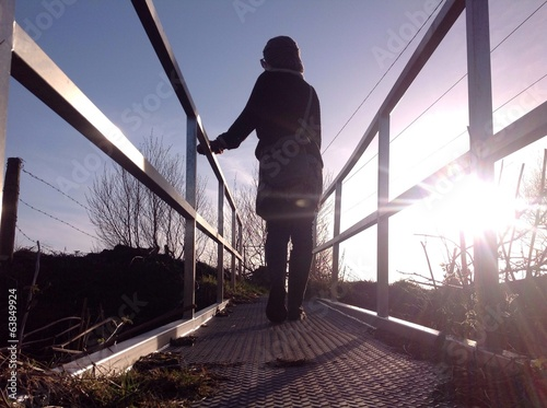 woman crossing rural footbridge in the evening