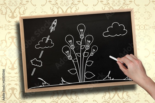 Composite image of hand drawing light bulb plant with chalk