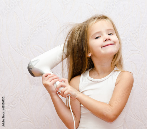 Cute smiling Little girl dries hair