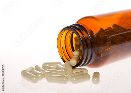 Open bottle of pills with pills out of the bottle