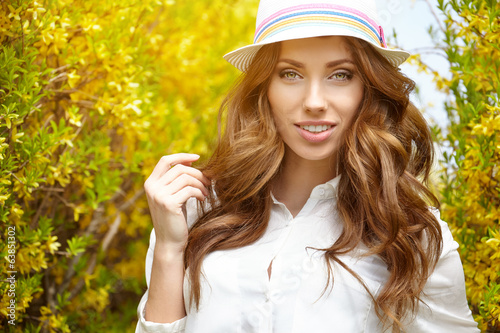 Spring woman in summer day walking in yellow park
