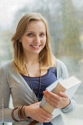 Happy student holding books by window