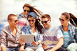 group of smiling teenagers looking at tablet pc