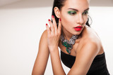 Beautiful woman in jewellery sitting over white - 63851598