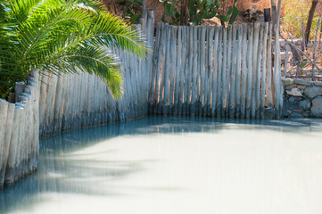 Therapeutic mud bath, surrounded by a wooden fence