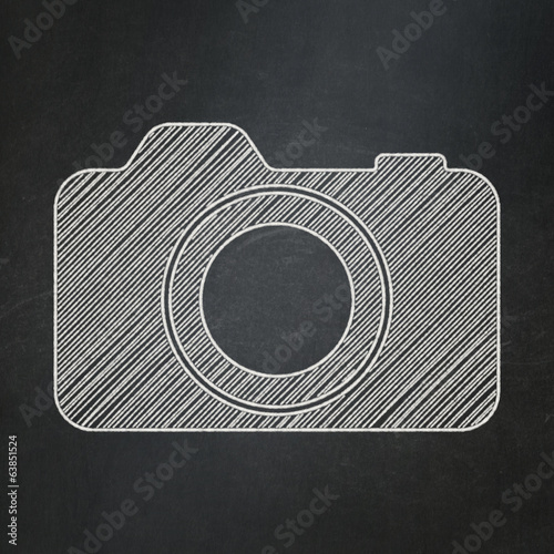 Tourism concept: Photo Camera on chalkboard background