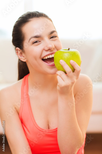 smiling teenage girl with green apple at home