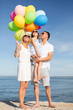 happy family with colorful balloons at seaside