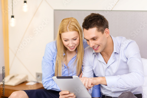 couple with tablet pc computer in hotel room