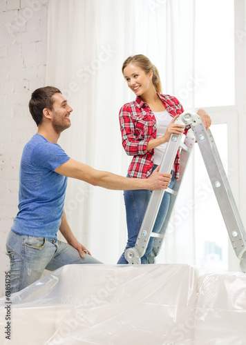 smiling couple hanging curtains