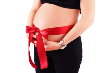 Belly of pregnant woman with red ribbon and bow