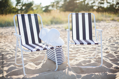 two beach lounges with beach bag and white hat