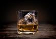 Glasses of whiskey on wood background.