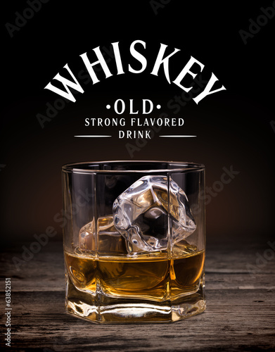Glasses of whiskey on wood background.