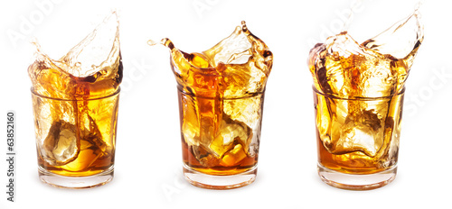 Glasses of whiskey with a splash on a white background.
