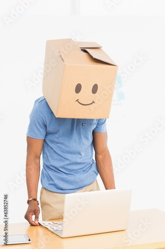 Man with happy smiley box over face in front of laptop