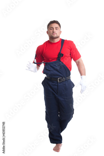 Handsome young man taking off his overalls