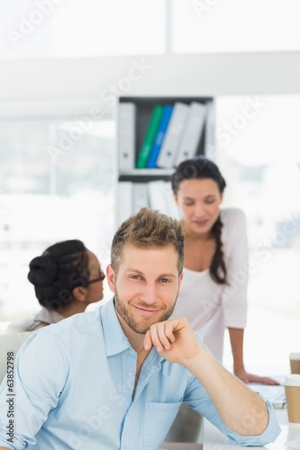 Handsome man smiling at camera while colleagues chat at desk