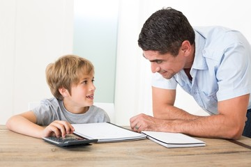 Father looking at son doing homework
