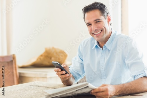 Smiling casual man with newspaper and cellphone in kitchen