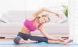 Fit blonde stretching on exercise mat smiling at camera