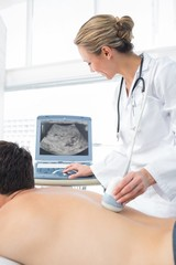 Doctor using sonogram on back of male patient