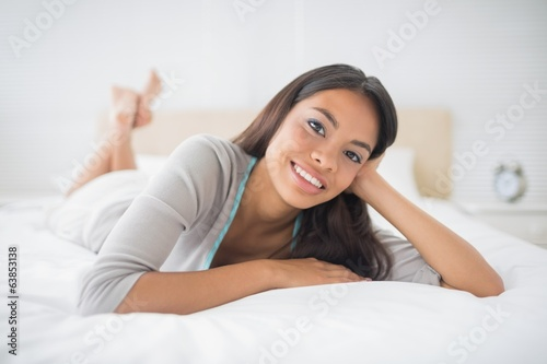 Pretty girl lying on bed smiling at camera