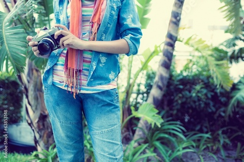 Woman wearing denim holding camera outside