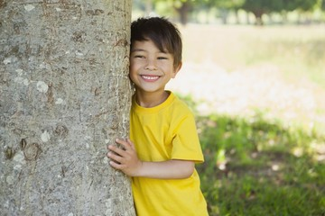 Cheerful boy standing by tree at park