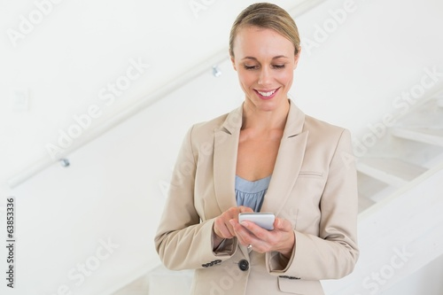 Smiling estate agent sending a text message