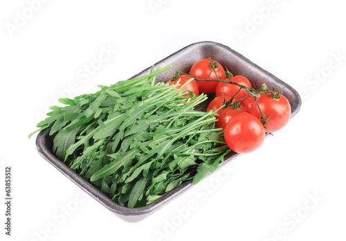 Tomatoes and arugula in plastic box.