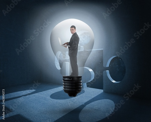 Composite image of businessman holding laptop in light bulb