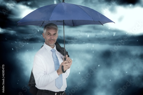 Composite image of businessman holding blue umbrella
