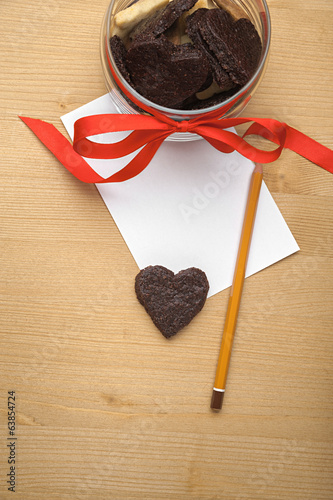 Chocolate cookie-heart on a piece of paper with pencil