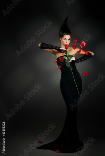 mysterious woman in dark hood with rose