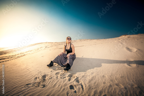 woman in long skirt sitting on sand dune