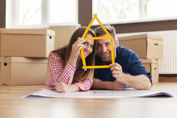 Couple in new apartment with home sign