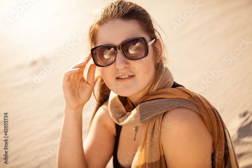 brunette woman in sunglasses at sunny day in desert