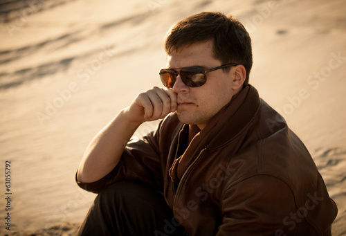 portrait of handsome man in sunglasses sitting on sand dune